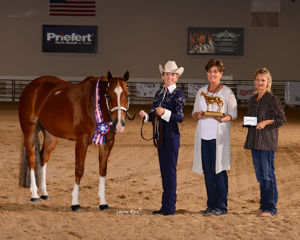 "Marian (left) and ""Ace"" accepting their championship prizes: a ribbon, trophy, and buckle. Also pictured is Ace's trainer and breeder."